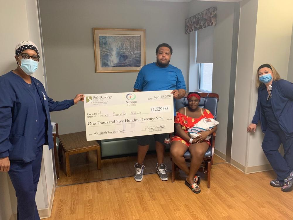 """The Vintson family receives a contribution for their new son's Path2College 529 Plan due to the fact that he was the first """"Tax Day Baby"""" at The Medical Center, Navicent Health."""